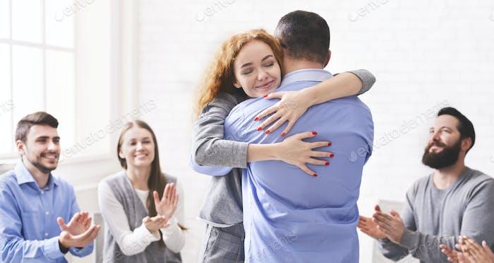 Glückliches Paar Umarmung nach erfolgreicher Gruppentherapie in der Ehe Berater Büro