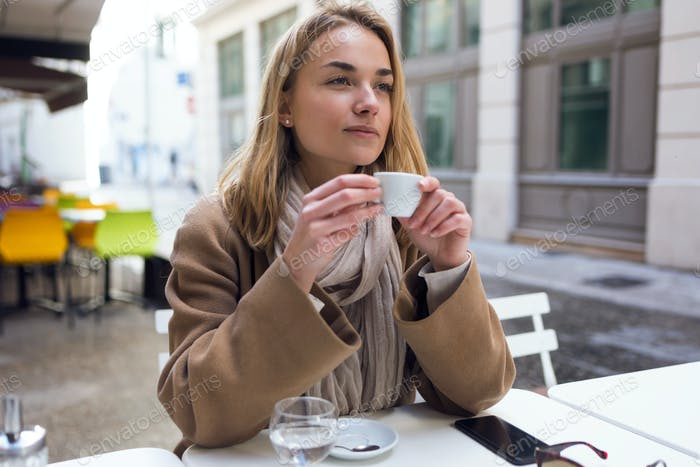 Ziemlich junge Frau seitwärts beim Trinken Tasse Kaffee