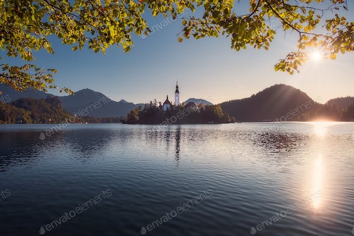Scenic view of Lake Bled and island with church, colorful autumn foliage, Slovenia