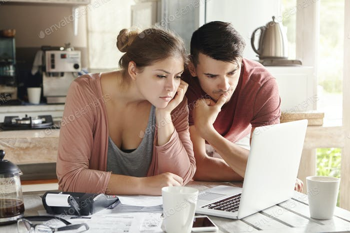 Young man and woman working together on laptop, paying utility bills via internet or using online mo