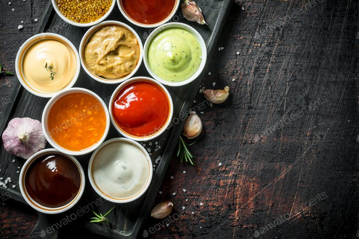 Different types of sauces in bowls on a cutting Board with garlic.