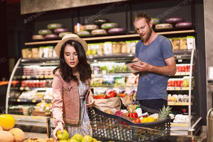 Young man thoughtfully reading shopping list while pretty girl i