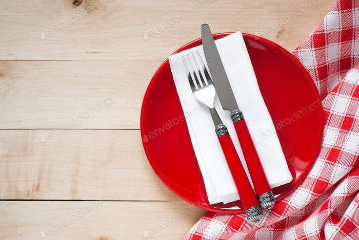 Table setting with a plate, cutlery and napkin