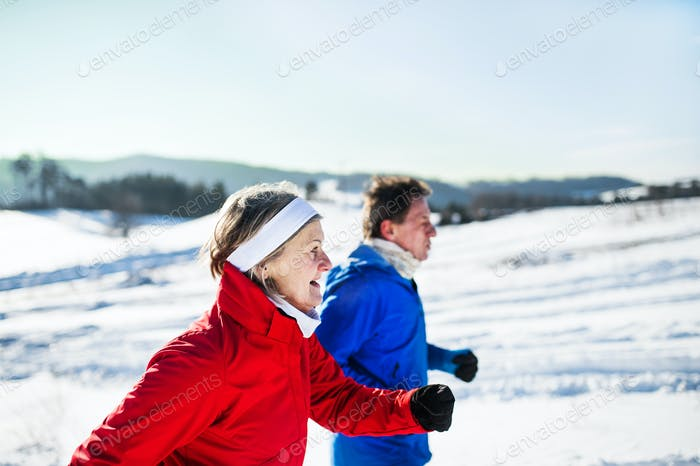A side view of senior couple jogging in snowy winter nature.