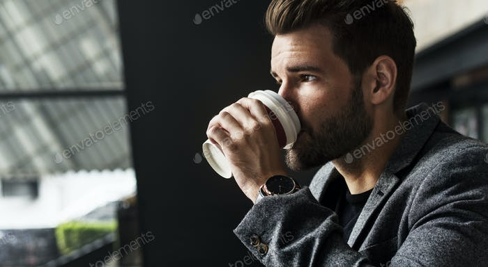 Side view of mna drinking hot coffee