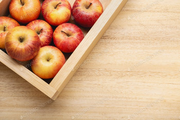 Apples in crate on wooden table