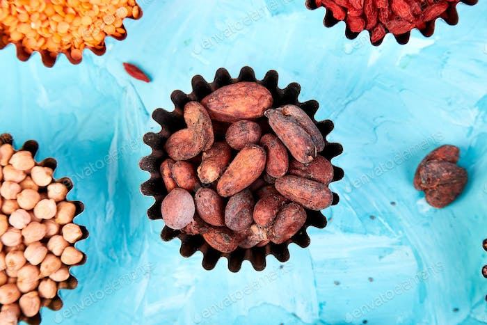 Various superfoods in small bowl on blue background