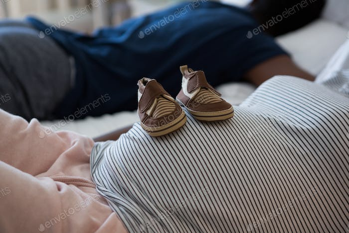 Pregnant woman relaxing with baby shoes on her belly in bedroom