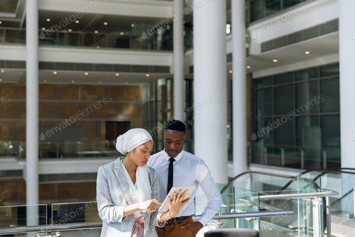 Male and female executives working on digital tablet in corridor