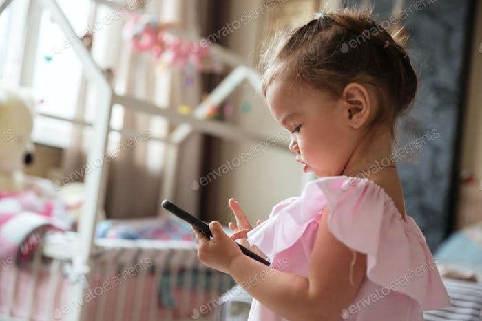 Concentrated little girl child indoors using mobile phone.