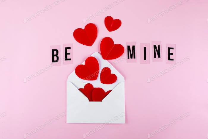 White envelope, red paper hearts and text Be Mine on pink background. Valentine's day, love concept