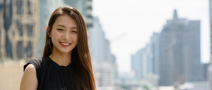 Happy young beautiful Asian businesswoman against view of the city