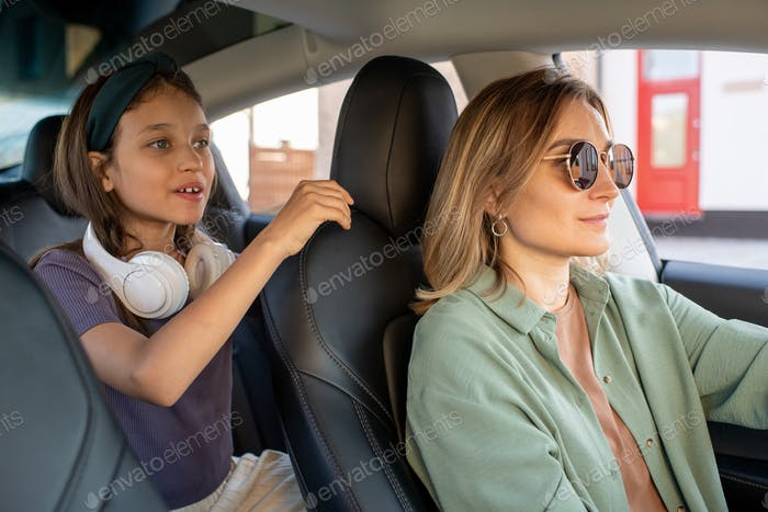 Cute little girl with headphones holding by seat of her mom driving car