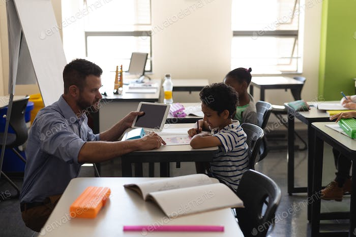 Young school teacher helping boy with study in classroom