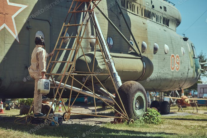 Mechanic in uniform and flying helmet carries out maintenance of a large military helicopter
