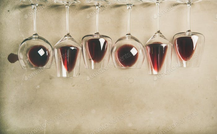 Red wine in different glasses over grey background, copy space