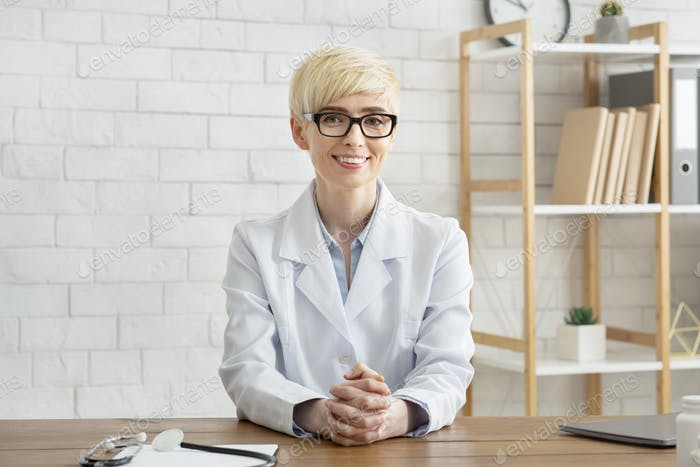 Visit to professional and health care. Smiling middle aged lady doctor sits at wooden table