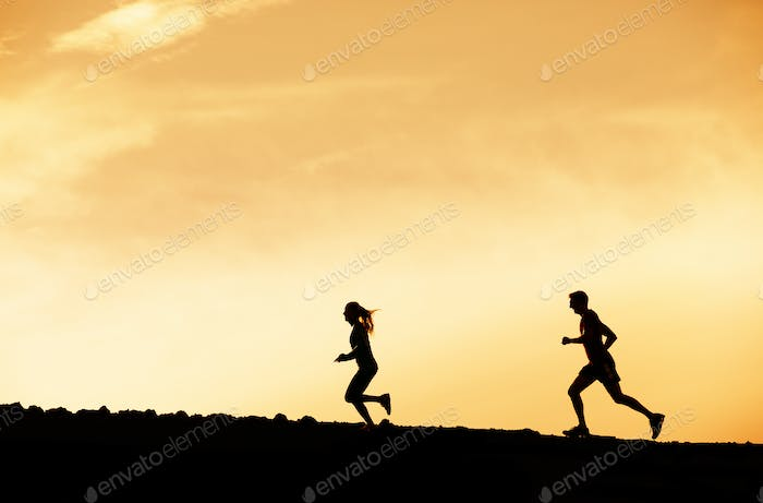 Man and woman runing together into sunset
