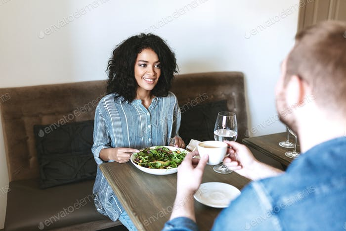 Young girl with dark curly hair have meeting with friend at cafe