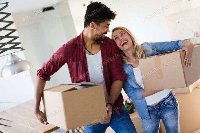 home, people, moving and real estate concept - happy couple having fun while moving in