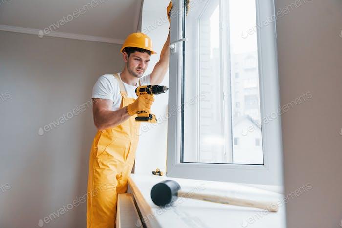 Handyman in yellow uniform installs new window by using automatic screwdriver