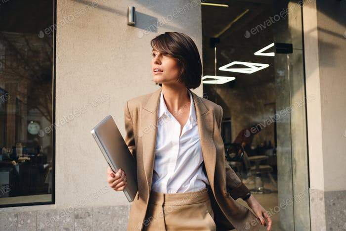 Side view of young stylish businesswoman with laptop thoughtfully looking away on city street