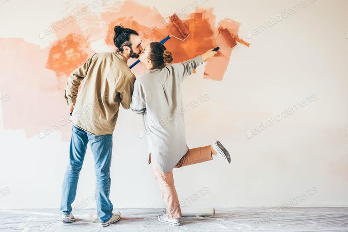 Couple renovating the house. Couple painting a wall