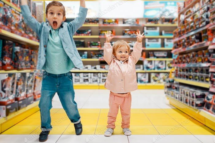 Boy and girl raised their hands up in kids store