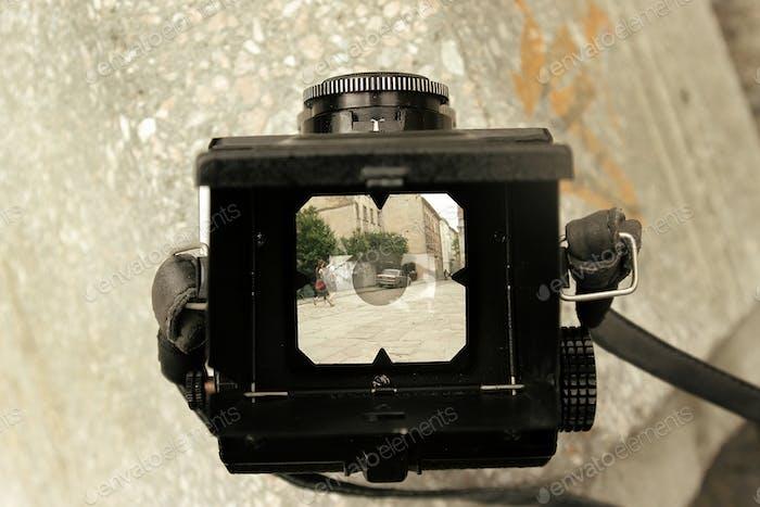 stylish analog film camera medium format on background of city street