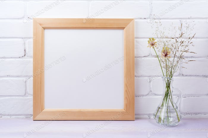 Wooden square frame mockup with grass in the glass jug