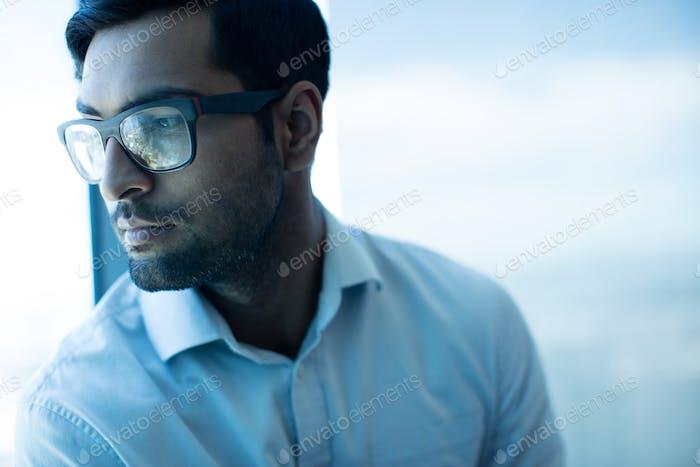 Thoughtful businessman looking away while wearing eyeglasses
