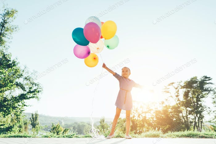 Smiling cute girl holding colorful balloons in the city park