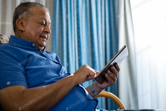 Low angle view of senior man using digital tablet in nursing home