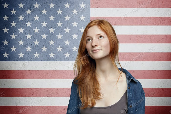 People, citizenship and patriotism. Portrait of attractive patriotic young woman with red hair, look