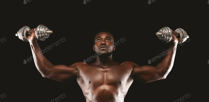 Concentrated black bodybuilder working out, pushing barbells up