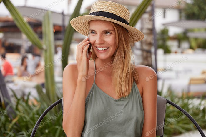 Adorable young woman with positive expression, dressed casually, has telephone conversation, dressed