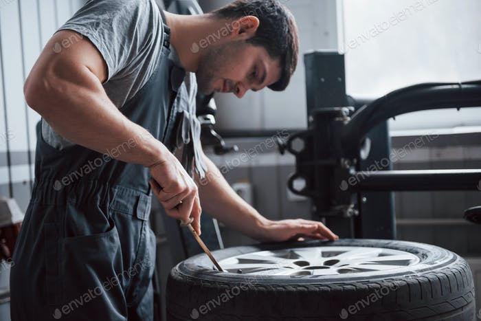 Pushing disc up. Young man works at the workshop at daytime