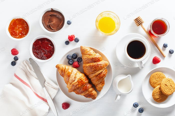 Continental breakfast with croissant, jam, chocolate spread and