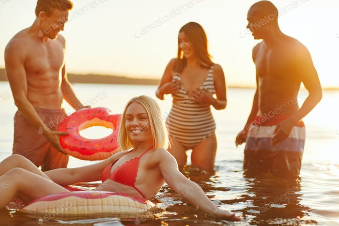 Diverse young friends in swimsuits having fun at a lake