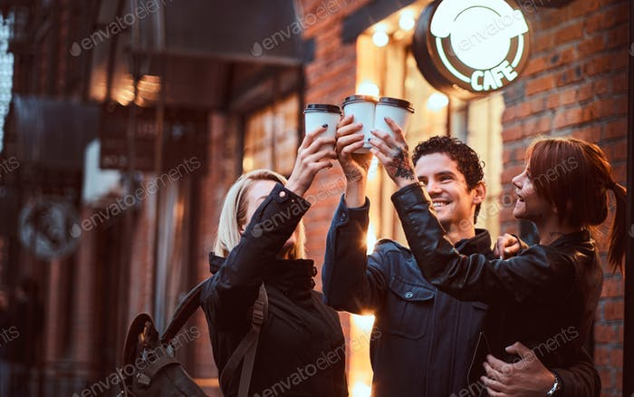 Cheerful friends making a toast with coffee near a cafe outside.