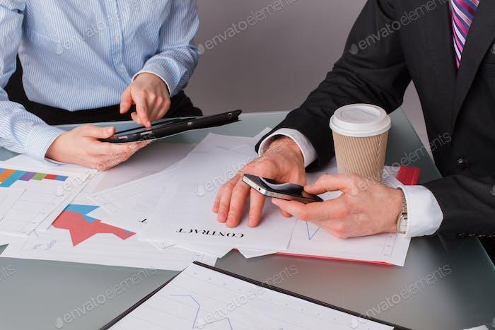 Dos empresarios analizando gráficos de ingresos en la oficina.