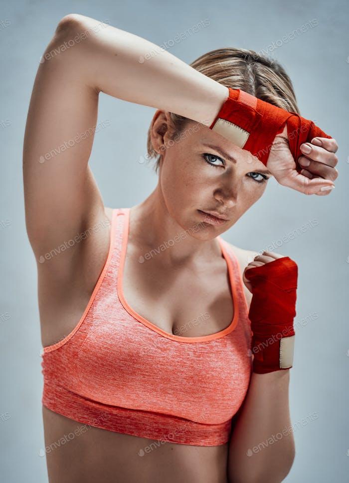 Sportliches erwachsenes weibliches Modell mit blonden Haaren und orangefarbenem Fitness-BH posiert in einem hellen Raum