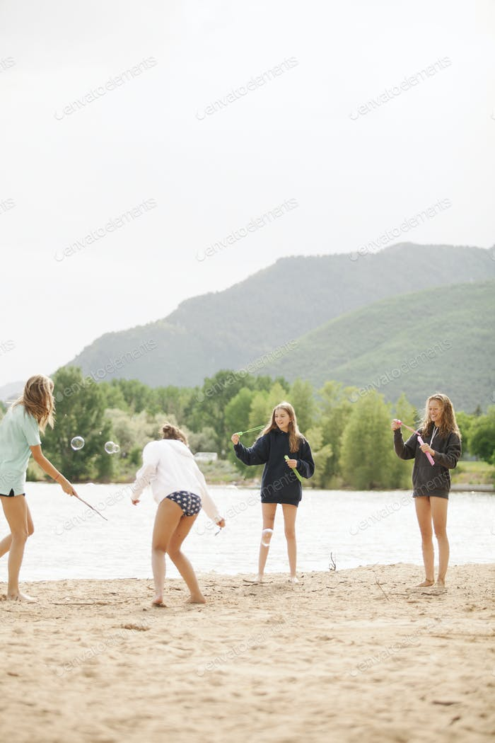 Teenage girls standing by a lake, surrounded by soap bubbles.