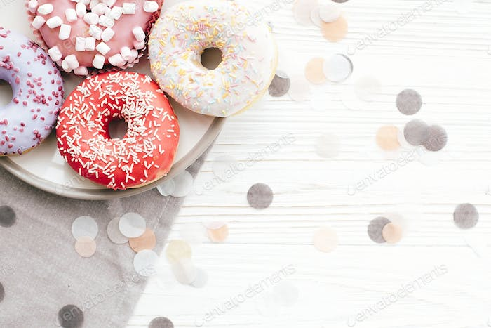 Delicious colorful donuts with sprinkles on stylish white table with confetti