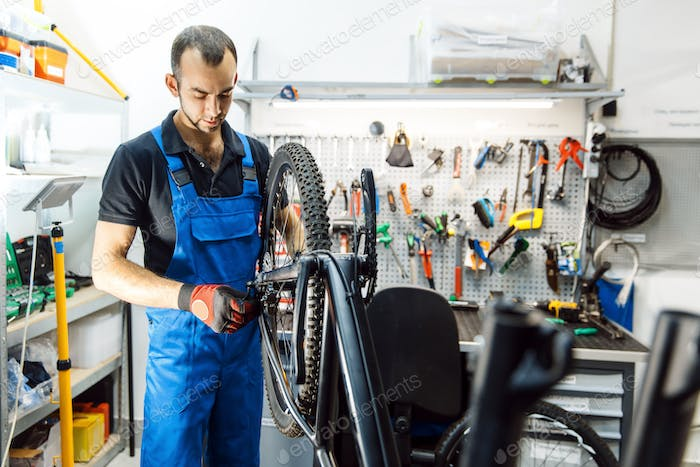 Bicycle assembly in workshop, man installs wheel