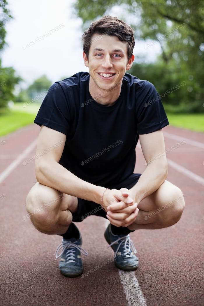 Portrait of handsome young male athlete crouching on track