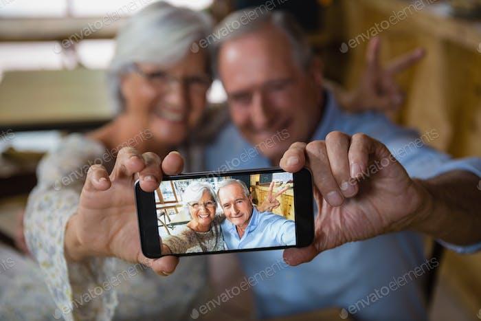 Happy senior couple taking selfie on mobile phone
