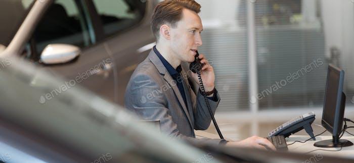 Salesman talking on landline phone in showroom