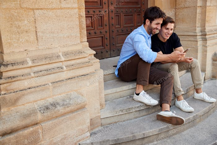 Male Gay Couple On Vacation Sitting Outdoors On Steps Of Building Looking At Mobile Phone