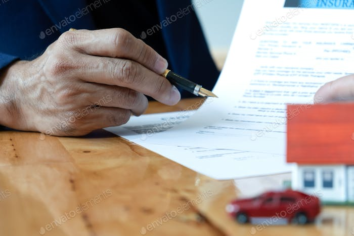 Broker house hold pen pointing at document.